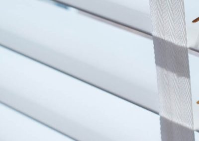 Winter white wooden venetian blind with contrasting tapes close up